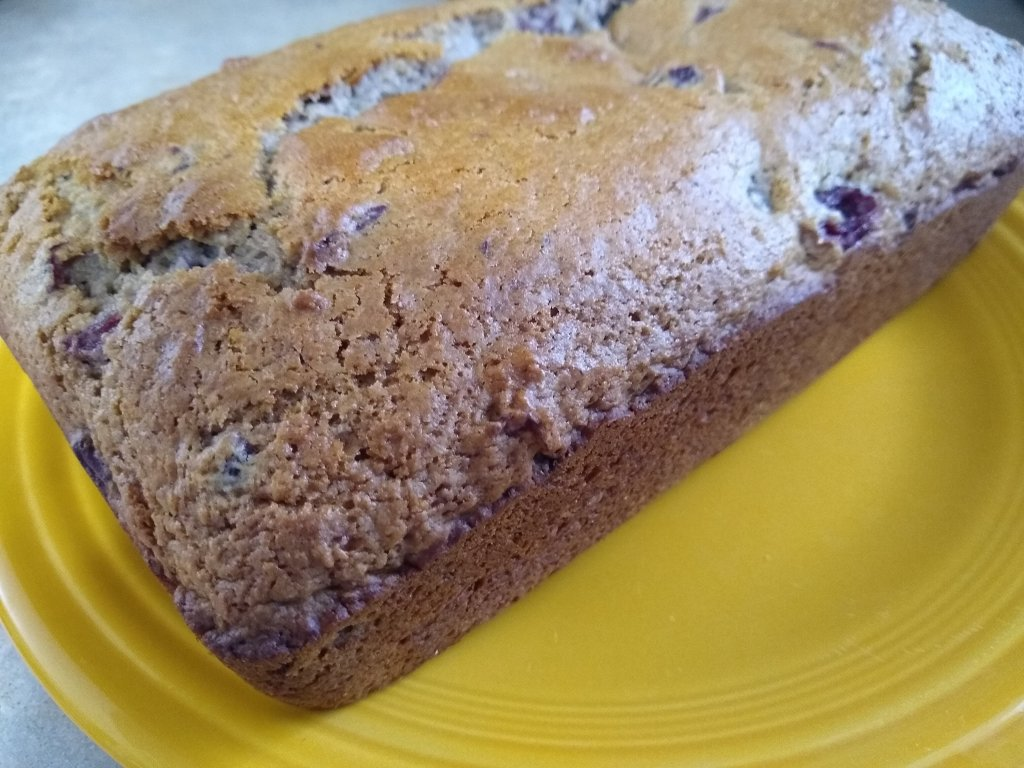 Whole loaf of old fashioned cranberry bread on a yellow Fiestaware plate.