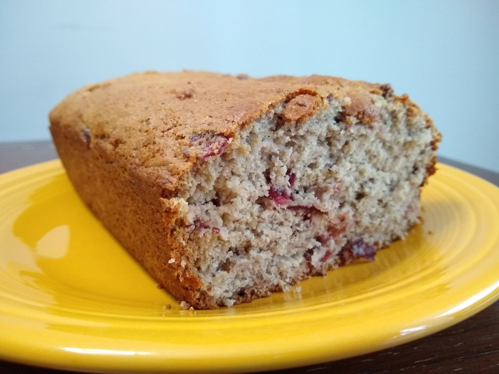 Cranberry bread sliced on yellow plate.