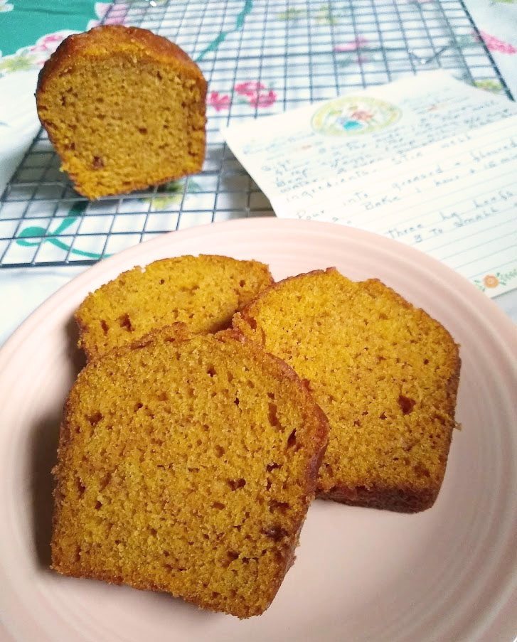 Pumpkin spice bread sliced with cut loaf and recipe card in the background.